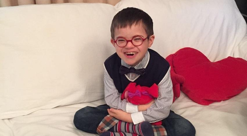 Bimbo con Sindrome di Down sorridente e con camicia a righe binche e blu, gilet e farfallino seduto in posizione yoga su un divano bianco con un cuore di pezza tra le braccia